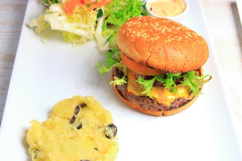 Hamburger met fijngestampte aardappel met truffels en slasalade stock fotografie