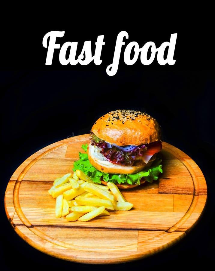 Hamburger met Frieten op een houten raad Snel voedsel stock afbeelding