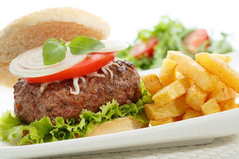 hamburger met gebraden gerechten die op wit worden geïsoleerdl stock afbeelding