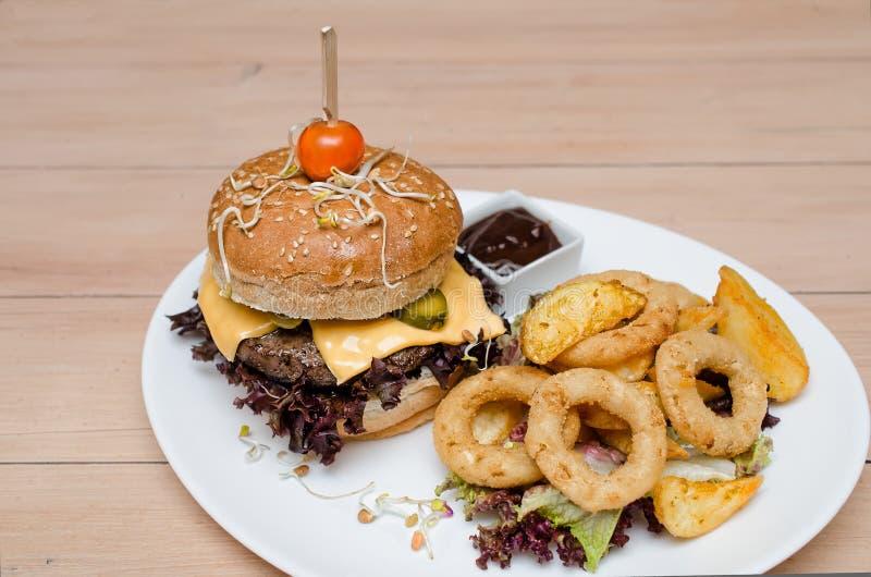 Hamburger met gebraden gerechten en uiringen stock afbeeldingen