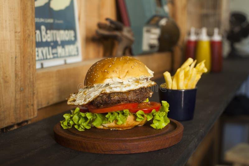 Hamburger met gebraden gerechten op houten lijst royalty-vrije stock fotografie