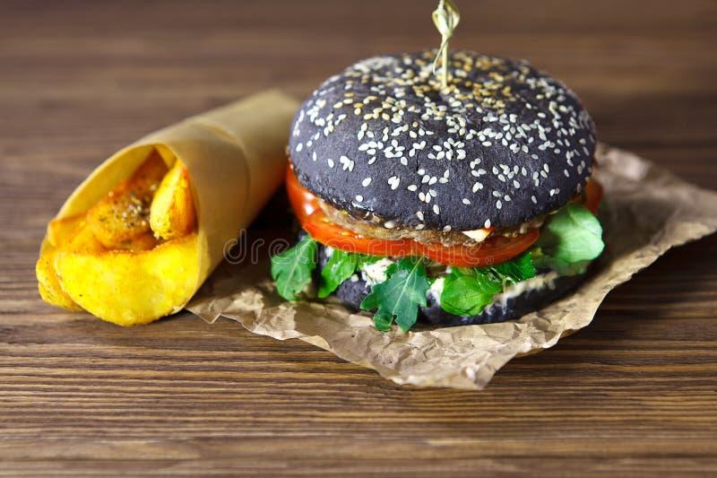 Hamburger met het zwarte broodje, op het kraftpapier-document met gebraden aardappels op bruine houten achtergrond stock foto