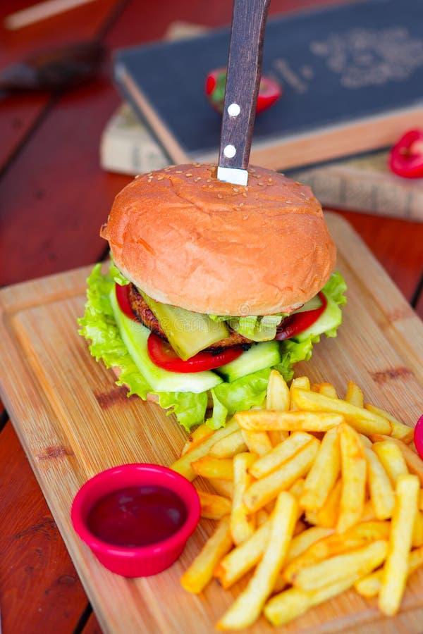 Hamburger met rundvlees, salade, sla, frieten, en ketchup met mes op houten raad stock foto