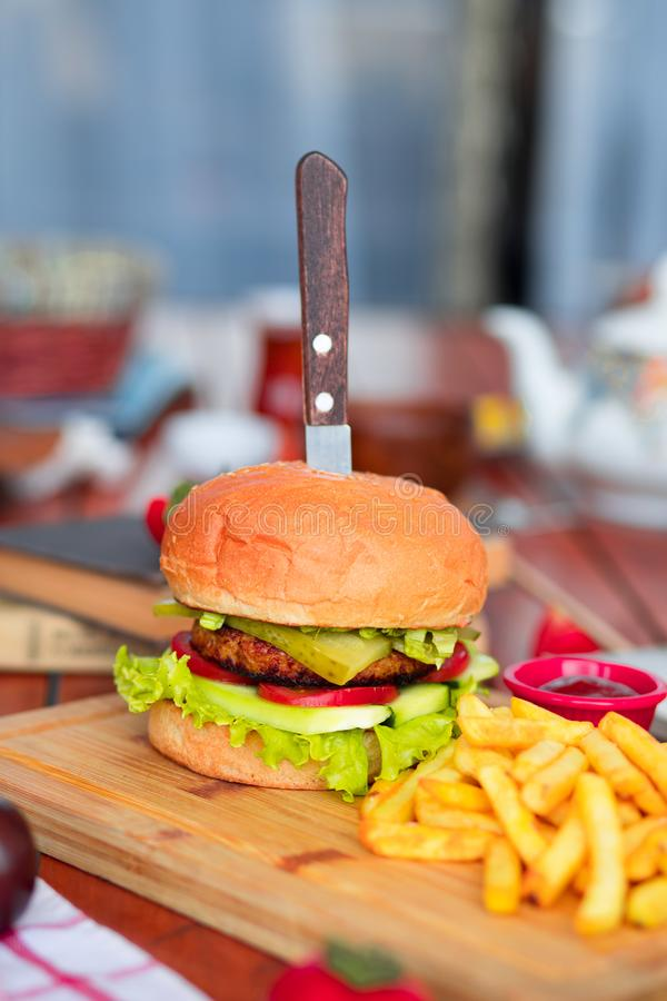 Hamburger met rundvlees, salade, sla, frieten, en ketchup met mes op houten raad stock foto's