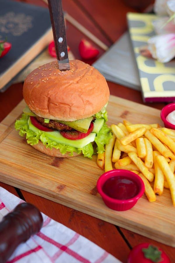 Hamburger met rundvlees, salade, sla, frieten, en ketchup met mes op houten raad stock fotografie