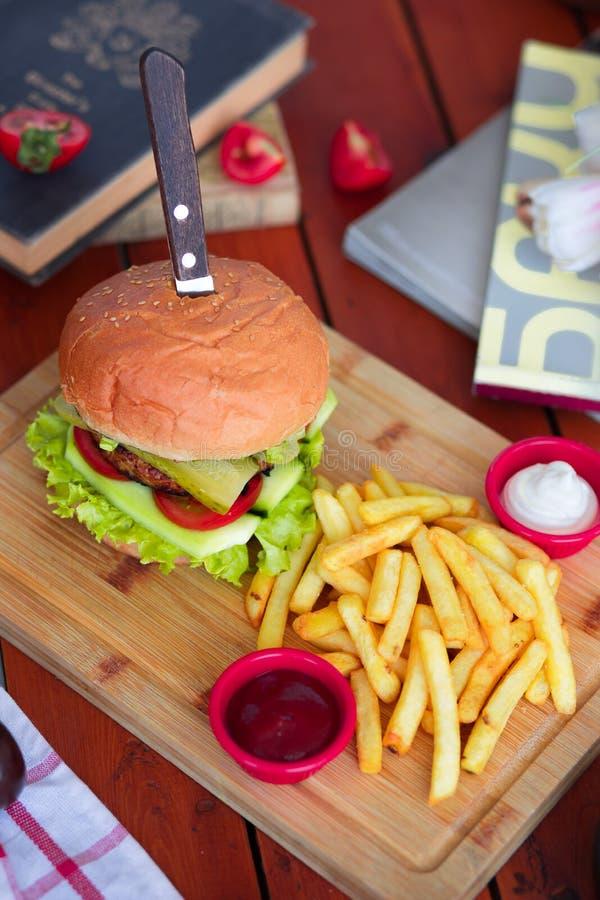 Hamburger met rundvlees, salade, sla, frieten, en ketchup met mes op houten raad royalty-vrije stock afbeelding