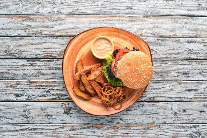 Hamburger met vlees, ui, tomaten en aardappelen in de schil Op de oude achtergrond Vrije exemplaarruimte royalty-vrije stock afbeeldingen