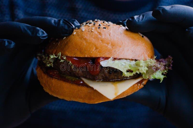 Hamburger mit Fleisch in den Händen eines Mannes in den schwarzen Gummihandschuhen stockbild