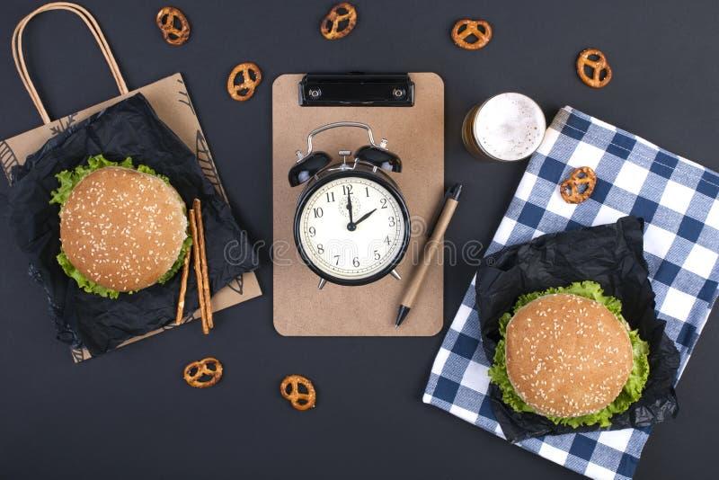 Hamburger na czarnym tle dla lunchu Notepad dla teksta i planowania Fast food i przekąski dla biura i szkoły Zegar w obraz stock