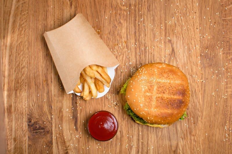 Hamburger na tabela de madeira com batatas fritas Refei??o deliciosa com ketchup fotografia de stock royalty free
