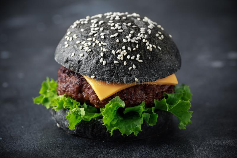 Hamburger nero con le foglie del formaggio, del manzo e dell'insalata verde Cheeseburger casalingo fotografia stock libera da diritti