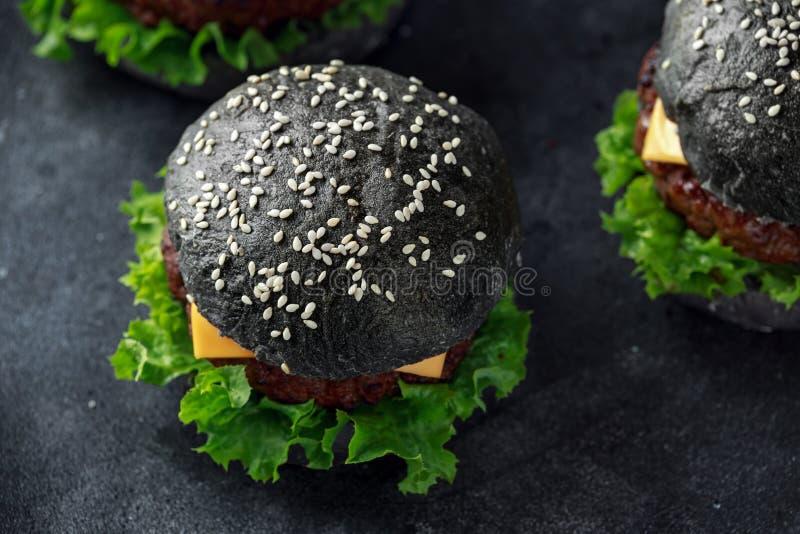 Hamburger nero con le foglie del formaggio, del manzo e dell'insalata verde Cheeseburger casalingo immagine stock