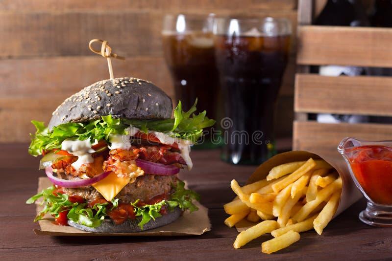Hamburger nero con manzo, formaggio, pomodori, cipolla rossa, bacon e patate fritte e cola su fondo di legno immagine stock