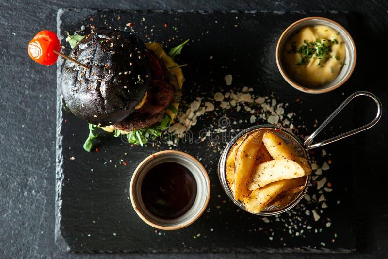 Hamburger nero delizioso del manzo con il soia SOS e le patate fritte fotografia stock