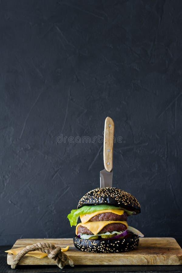 Hamburger nero su un tagliere di legno Vista laterale, fondo nero, spazio per testo fotografia stock libera da diritti