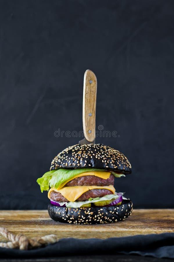 Hamburger nero su un tagliere di legno Vista laterale, fondo nero, spazio per testo immagini stock libere da diritti