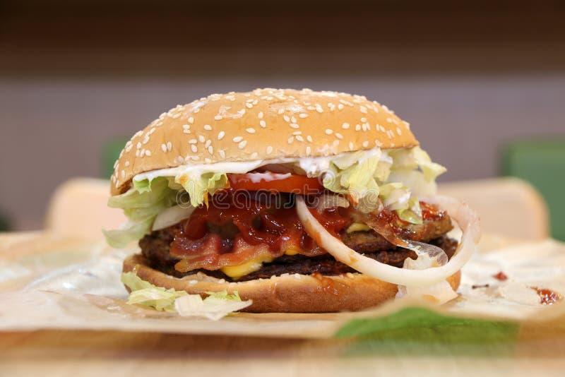 Hamburger no papel com pão redondo e sésamo, carne e vegetal brancos fotografia de stock