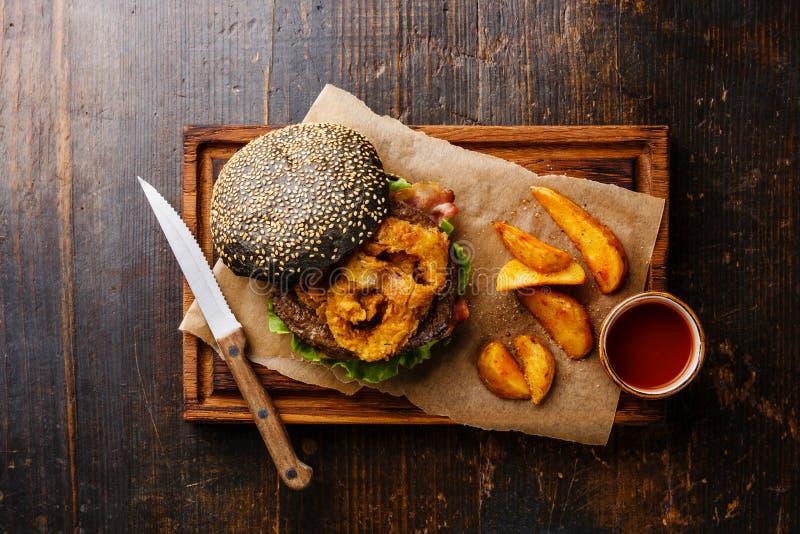 Hamburger noir avec de la viande, des fritures d'anneaux d'oignon et des cales de pomme de terre photo stock