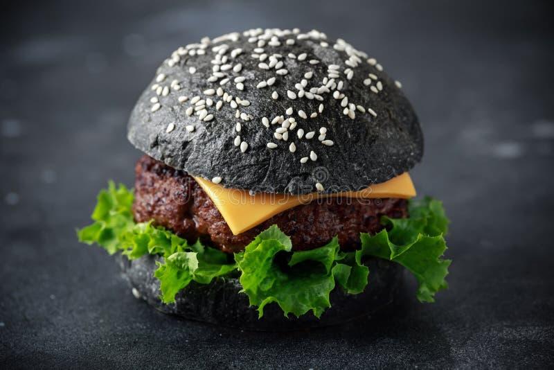 Hamburger noir avec des feuilles de fromage, de boeuf et de salade verte Cheeseburger fait maison photo libre de droits