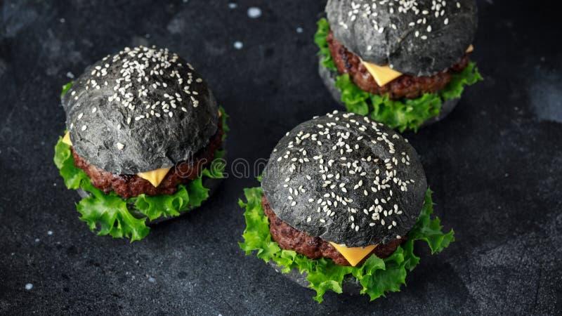 Hamburger noir avec des feuilles de fromage, de boeuf et de salade verte Cheeseburger fait maison photo stock