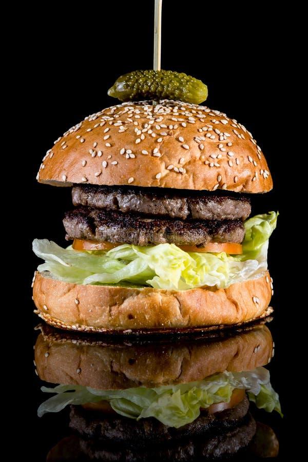 Hamburger nu savoureux frais avec la réflexion d'isolement sur le backg noir image libre de droits