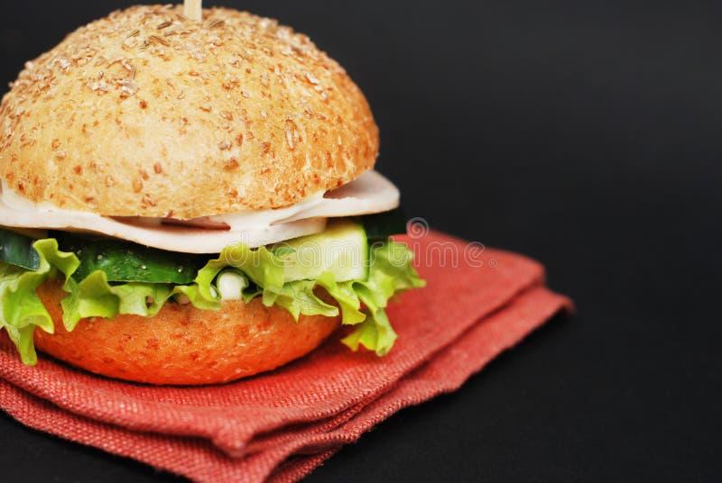 Hamburger ou hamburger fait maison de fromage sur la serviette orange au-dessus du fond noir Aliments de préparation rapide pour  photo libre de droits
