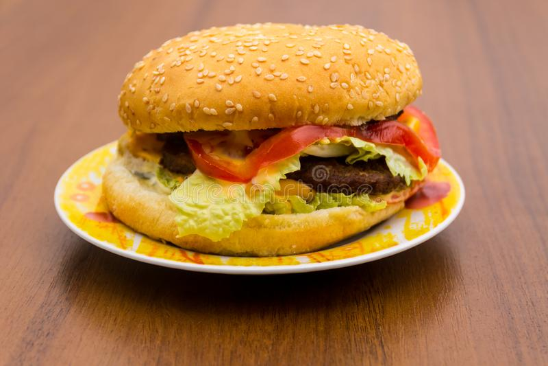 Hamburger ou sanduíche delicioso na placa na tabela de madeira fotografia de stock royalty free