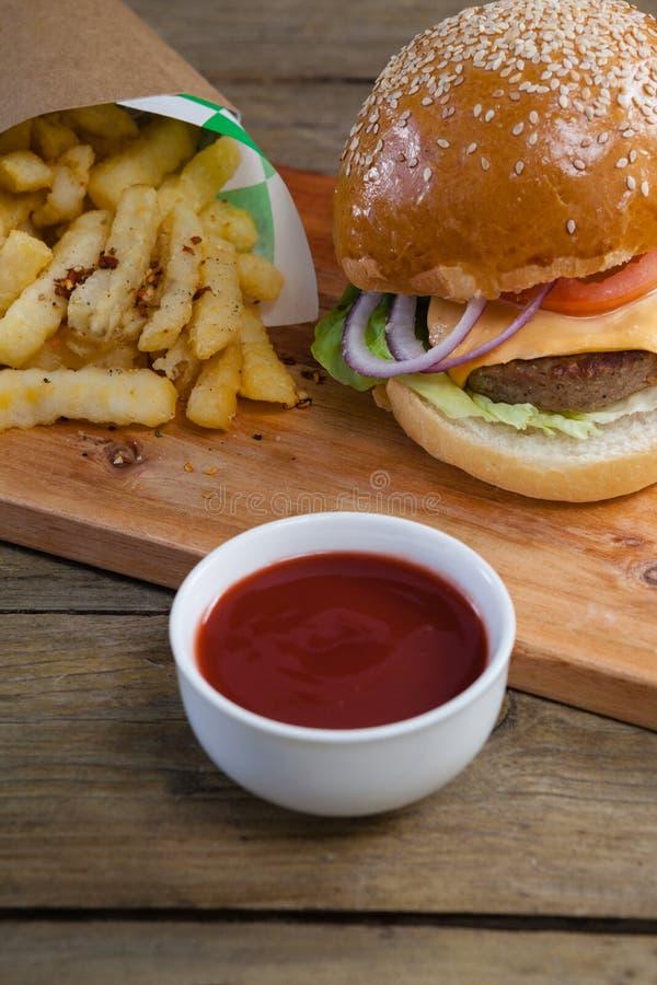 Hamburger, patate fritte e salsa al pomodoro sulla tavola immagine stock libera da diritti