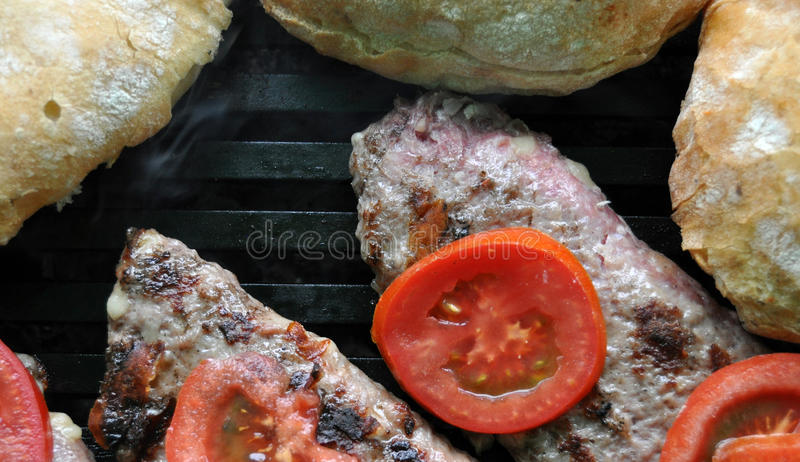Hamburger patties grilling on a barbecue. Picture of a Hamburger patties grilling on a barbecue with tomato and bread stock images