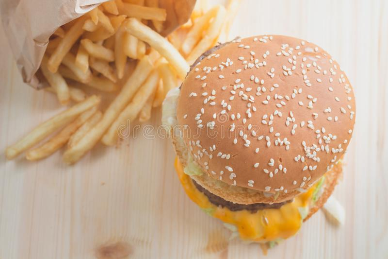 Hamburger placed on a wooden table. With potato chips stock image