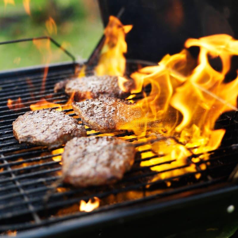 Hamburger que estão sendo grelhados com chamas imagens de stock royalty free