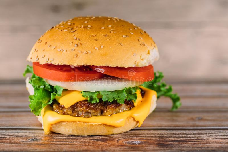 Hamburger sandwich with melted cheese, tomato, meat. Burger, hamburger sandwich with melted cheese, tomato meat, meal, sandwiches, appetizer, bun, fast, lettuce royalty free stock image