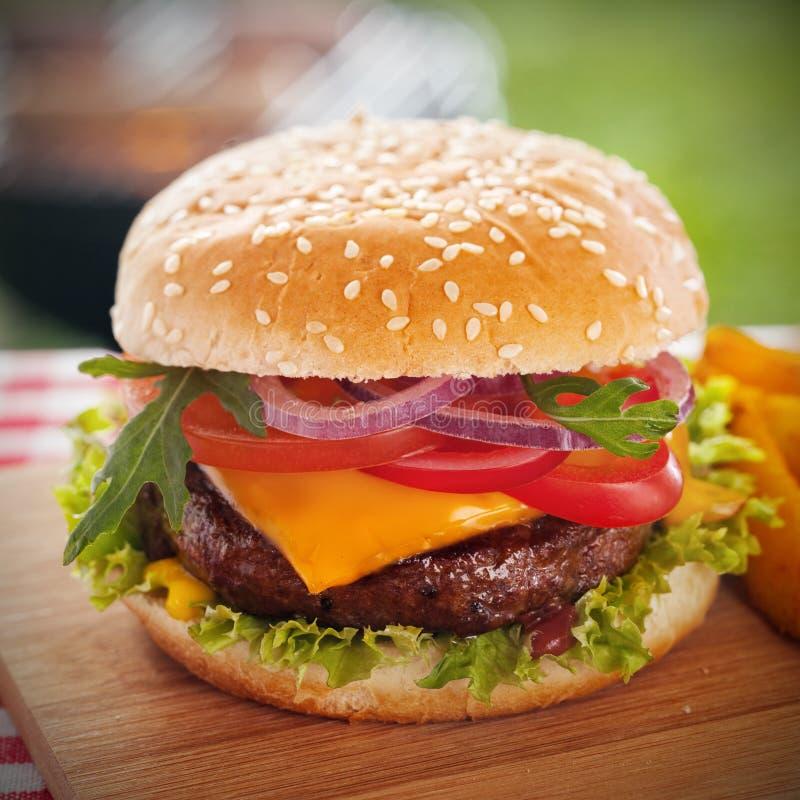 Hamburger saporito con formaggio fuso su un panino del sesamo immagini stock
