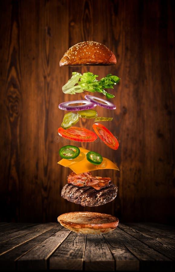 Hamburger savoureux avec des ingrédients de vol sur le fond foncé photo libre de droits