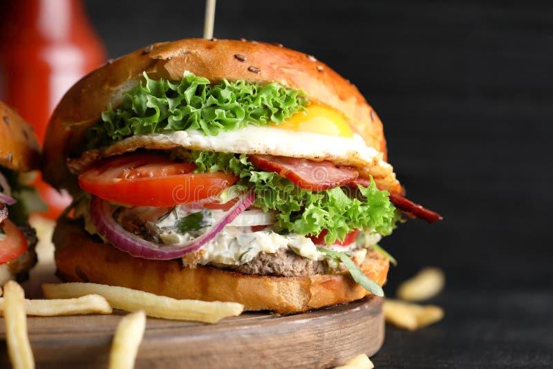 Hamburger savoureux avec l'oeuf au plat sur le conseil en bois photo libre de droits