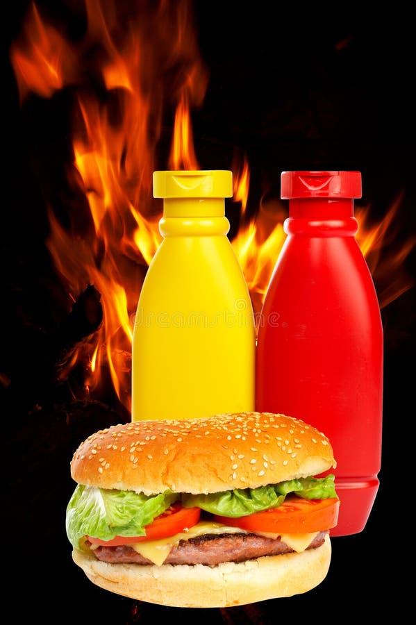 Hamburger sopra una priorità bassa delle fiamme immagine stock