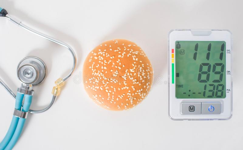 Hamburger, stethoscope and pressure gauge on a white background, top view stock photo