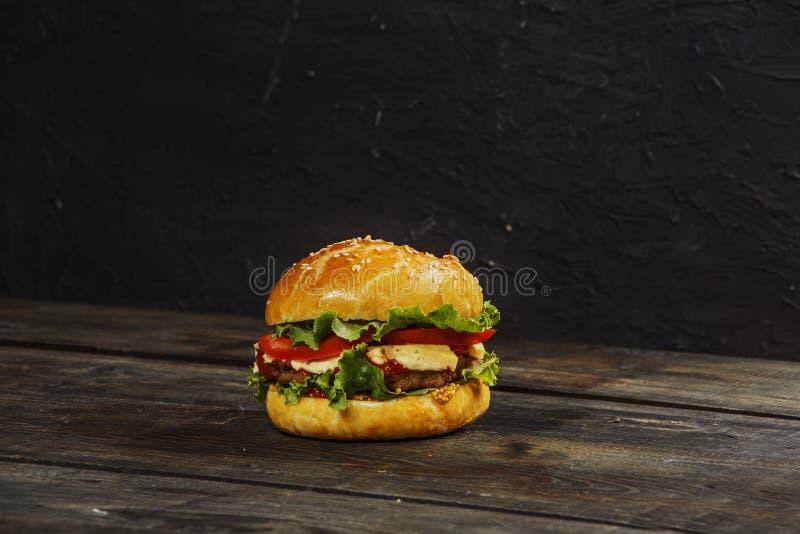 Hamburger su un bordo di legno contro un fondo scuro con lo spazio della copia Hamburger con salsa e gli ortaggi freschi su una t immagini stock libere da diritti