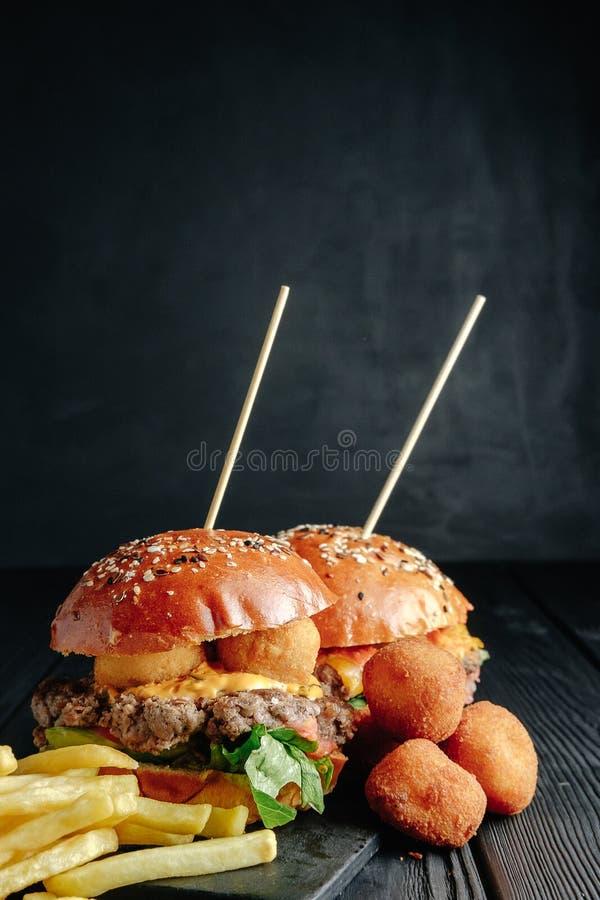 Hamburger succosi casalinghi sul bordo di legno, sulle palle del formaggio e sulle patate fritte fotografia stock libera da diritti