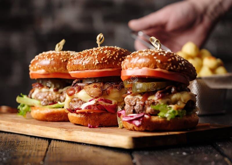 Hamburger succoso delizioso casalingo con manzo, formaggio, il pomodoro ed il Ca fotografie stock libere da diritti