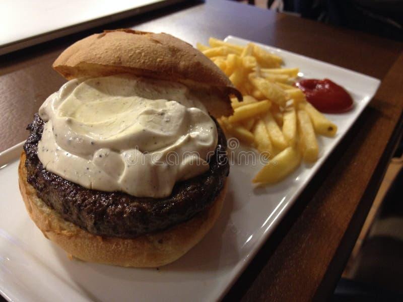 Hamburger suculento com molho, fritadas e ketchup imagens de stock