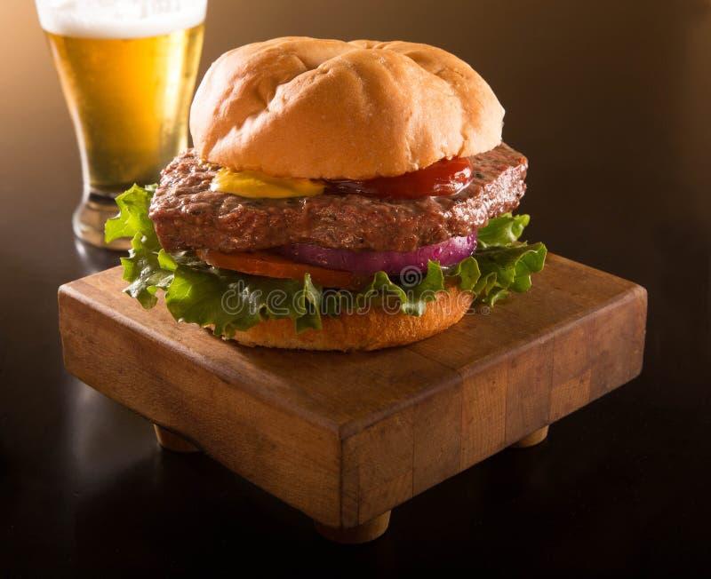 Hamburger sur un petit pain de kaiser avec de la bière image stock
