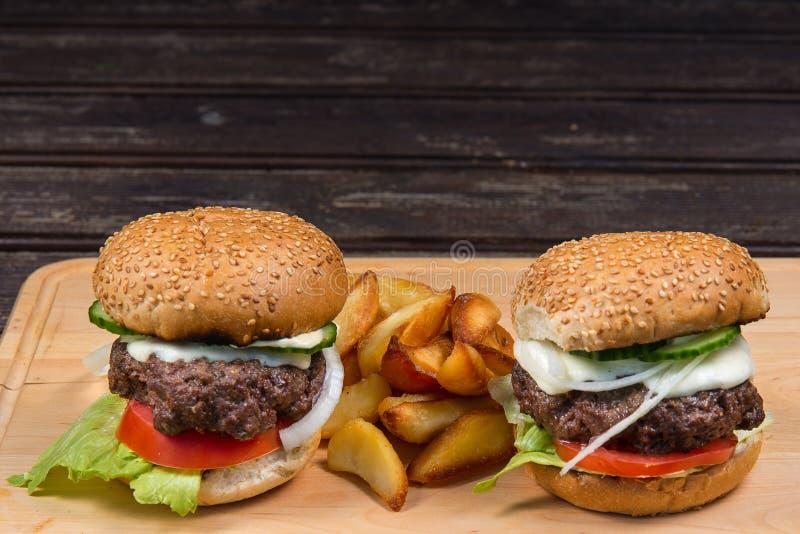 Hamburger und Pommes-Frites auf einer hölzernen Platte stockbild