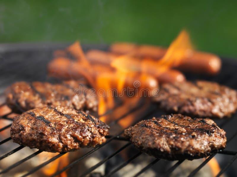 Hamburger und Würstchen, die draußen auf Grill kochen stockbild