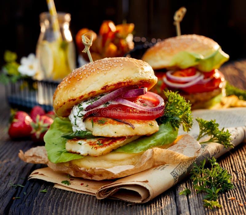 Hamburger végétarien avec du fromage grillé de halloumi, la laitue fraîche, la tomate, le concombre et l'oignon en plus de la sau photographie stock