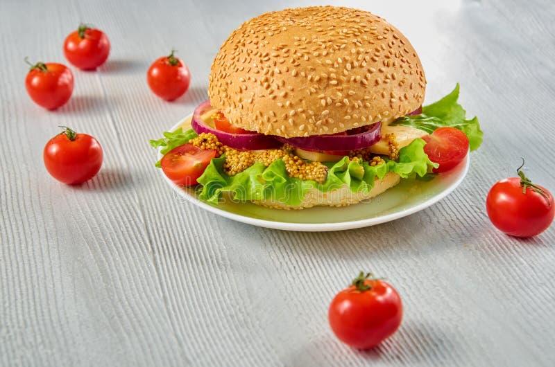 Hamburger vegetariano casalingo con insalata, gli anelli di cipolla, il formaggio e la senape decorati con i pomodori ciliegia su fotografia stock libera da diritti