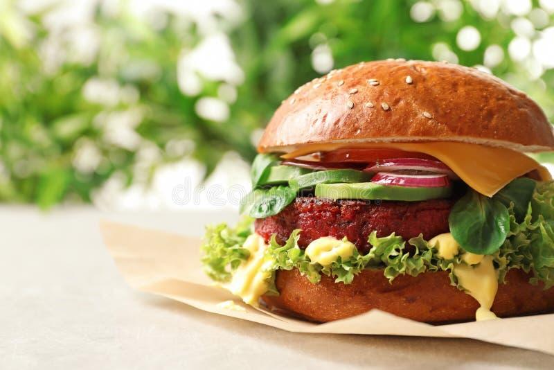 Hamburger vegetariano saporito con la cotoletta della barbabietola sulla tavola contro fondo vago immagini stock
