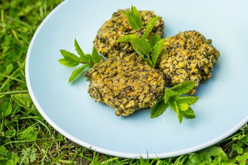 Hamburger verdi del vegano della lenticchia su un piatto blu immagini stock