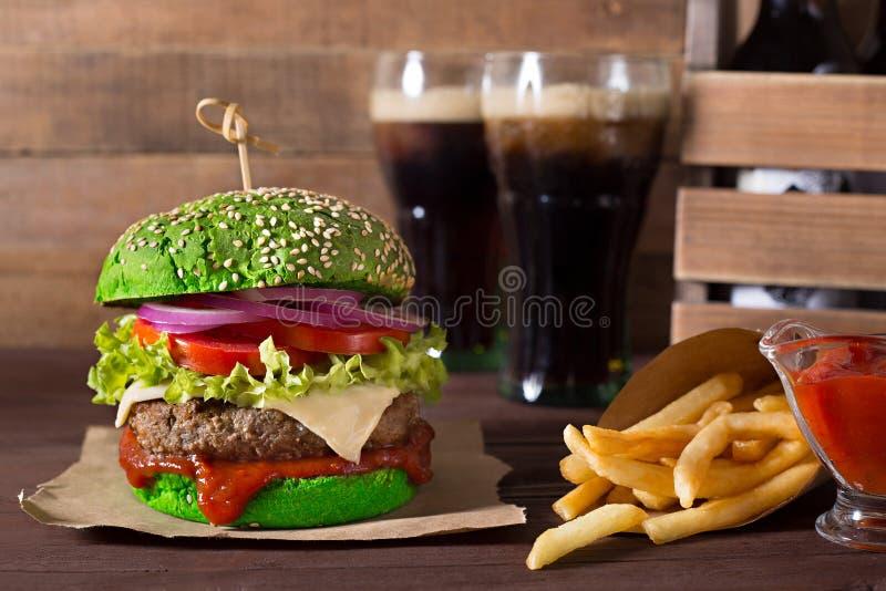 Hamburger vert de boeuf avec la pomme frite et le kola sur le fond en bois photo libre de droits
