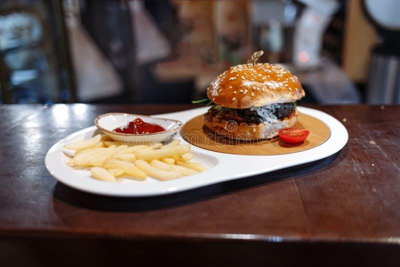 Hamburger verzierte Tomate, Pommes-Frites und Tomatensauce in einer ovalen Platte auf einem Holztisch stockbild